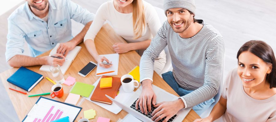 Top view of group of business people in smart casual wear working together and smiling while sitting at the wooden desk